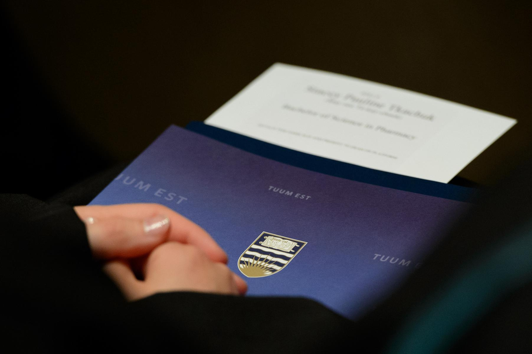 A graduate's hands holding a UBC graduation event program, from the spring 2014 congregation. Photo credit: Don Erhardt / UBC Communications & Marketing