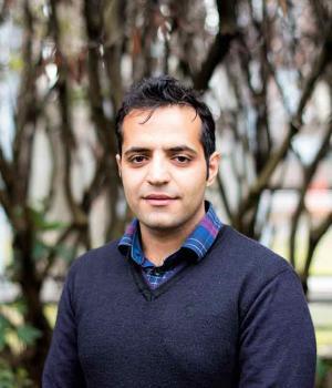 Mohammad Karamouzian poses in front of trees